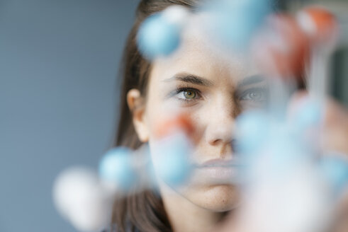 Female scientist studying molecule model, looking for solutions - KNSF05646