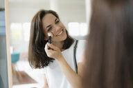 Pretty woman applying make up, using mascara - KNSF05667