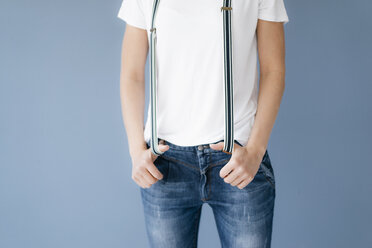 Woman stretching suspenders with her thumbs - KNSF05670