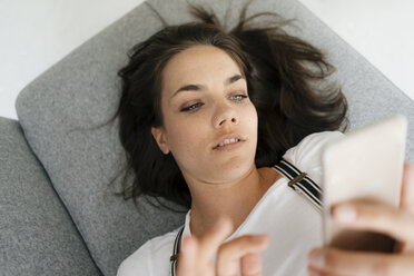 Woman lying on couch, using smartphone - KNSF05673