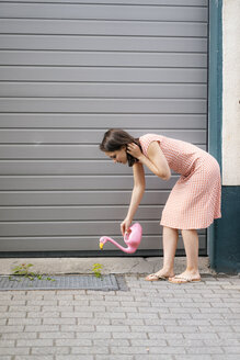 Woman watering plants with a flamingo can in an urban street - KNSF05694