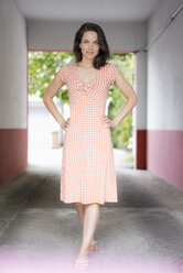 Pretty woman standing in driveway with hands on hips - KNSF05700