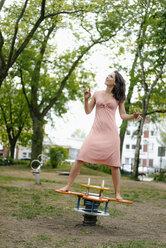 Woman balancing on a seesaw on a playground - KNSF05703