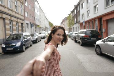 Woman walking in street, holding hand of a man - KNSF05715