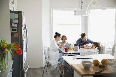Family in pajamas enjoying breakfast using digital tablet - HEROF25087
