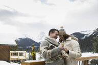 Couple enjoying champagne on snowy deck below mountains - HEROF25117