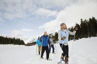 Couples snowshoeing in snowy field - HEROF25120