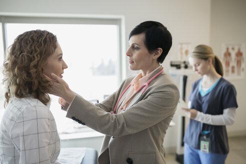 Doctor checking patients glands in examination room - HEROF25180