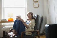 Portrait of woman relaxing drinking coffee in armchair - HEROF25336