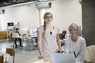 Portrait of confident businesswomen working at laptop office - HEROF25363