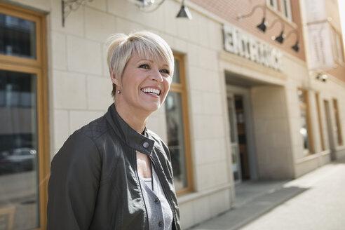 Smiling blonde woman at urban storefront - HEROF25372