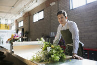 Portrait florist arranging bouquet craft paper flower shop - HEROF25390