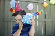 Boy wearing birthday party hat shaking wrapped gift - HEROF25510