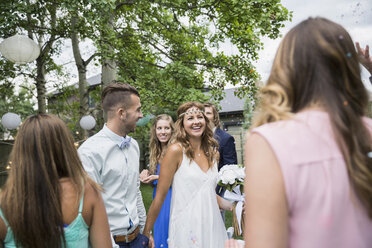 Bride and groom surrounded by friends backyard wedding - HEROF25522