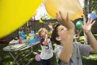 Boys playing with balloons at backyard birthday party - HEROF25531