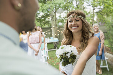 Bride with bouquet smiling at groom backyard wedding - HEROF25534