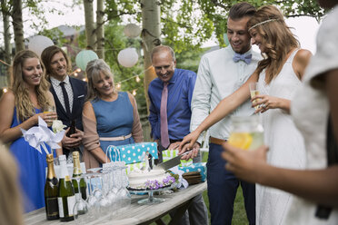 Bride and groom cutting cake backyard wedding reception - HEROF25537