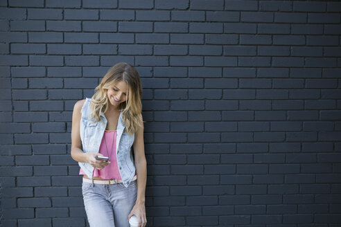 Blonde woman texting with cell phone brick wall - HEROF25552