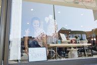 Worker placing open sign in shop window - HEROF25603