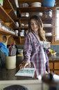 Woman using digital tablet drinking coffee in kitchen - HEROF25675