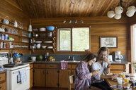 Young couple enjoying breakfast at cabin kitchen table - HEROF25678
