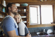 Young couple hugging in cabin kitchen - HEROF25726