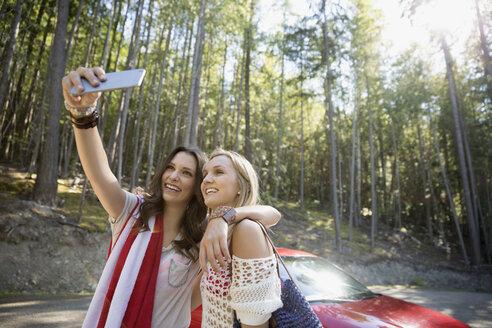 Young women taking selfie outside car in woods - HEROF25744
