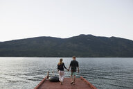 Young couple holding hands walking on lake dock - HEROF25795