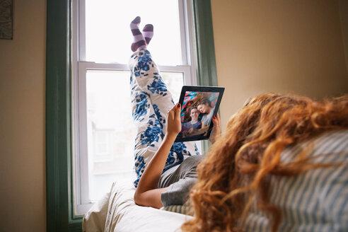 Teenage girl using digital tablet in bed - TGBF01915