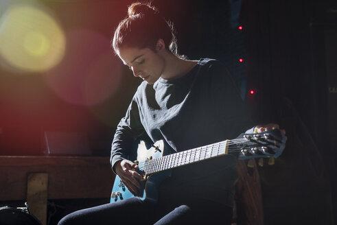 Serious Woman Practicing Guitar At Recording Studio - TGBF02065