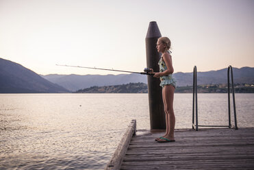 Side view of girl fishing in lake while standing on pier against clear sky during sunset - CAVF60661