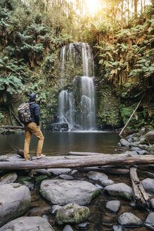 Rear view of hiker with backpack looking at waterfall while standing on driftwood in forest - CAVF60667