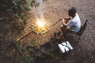 High angle view of hiker sitting on camping chair by campfire in forest - CAVF60670