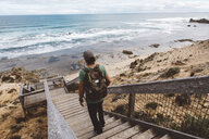 Rear view of hiker with backpack walking down wooden steps at beach - CAVF60673