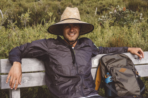 Portrait of smiling hiker with backpack wearing straw hat while sitting on bench at Wilsons Promontory National Park - CAVF60694