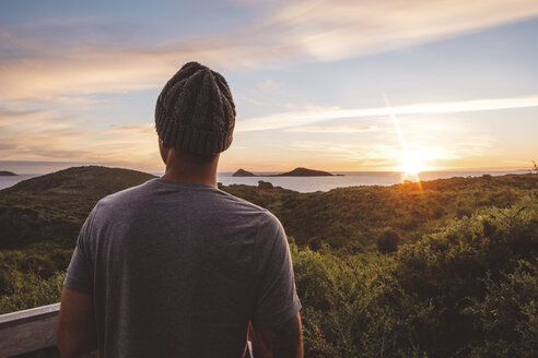Man wearing knit hat looking at view against sky during sunset - CAVF60697