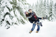 Playful boyfriend piggybacking girlfriend while standing on snow covered field in forest - CAVF60724