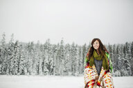 Low angle view of smiling woman looking away with blanket standing against sky in snow covered forest - CAVF60727