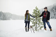 Happy couple holding pine tree while standing on snow covered field against sky in forest - CAVF60730