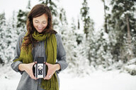 Smiling woman holding camera while standing against snow covered pine trees in forest - CAVF60736