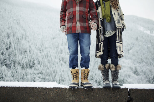 Low section of couple holding hands while standing on retaining wall against mountain during winter - CAVF60739