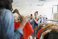 Woman photographing friend holding shirt in clothing shop - HEROF25814