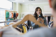 Woman photographing friend holding shirt in clothing shop - HEROF25817