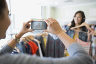 Woman photographing friend holding dresses in clothing shop - HEROF25820