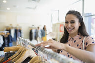 Smiling woman browsing clothing rack in shop - HEROF25823