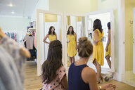 Woman trying on dress for friends clothing shop - HEROF25829
