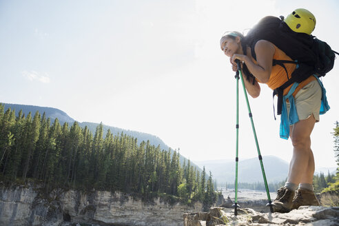 Woman backpacking leaning on hiking poles - HEROF25853