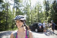 Smiling woman wearing mountain biking helmet - HEROF25868