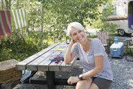 Smiling senior woman at campsite picnic table - HEROF25871