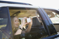 Woman photographing with camera phone from car window - HEROF25910